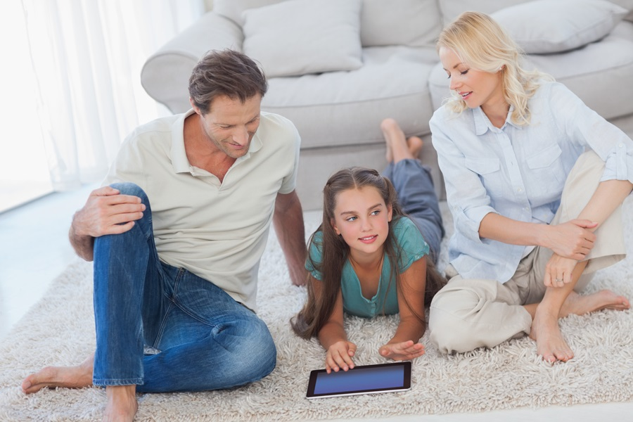 Young girl and her parents using a tablet lying on a carpet